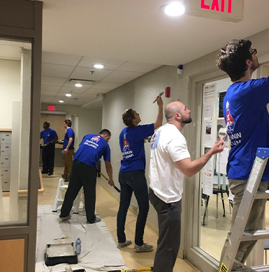Group of volunteer paint a hall way